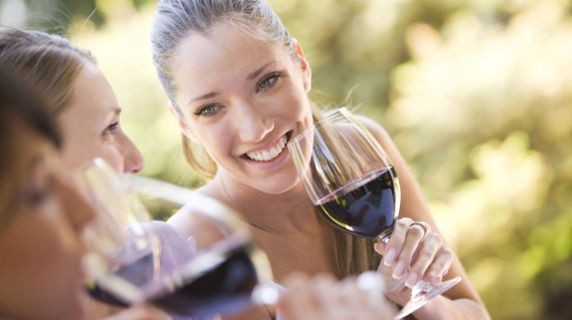 Drei fröhliche junge Frauen sitzen draußen zusammen und trinken Rotwein.