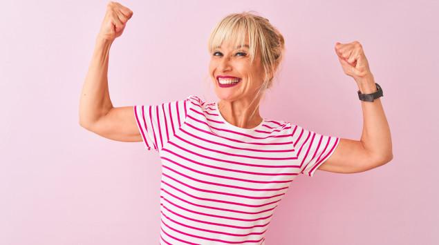 Eine jung gebliebene Frau zeigt die Muskeln und lacht