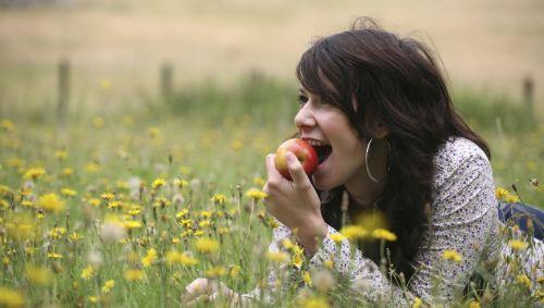 Eine junge Frau liegt in einer Blumenwiese und beißt in einen Apfel.