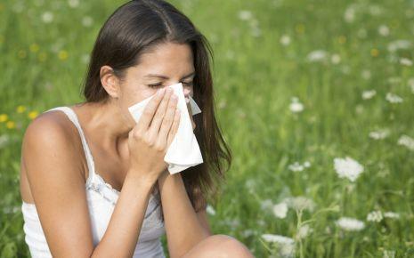 Eine Frau sitzt inmitten einer Sommerwiese und putzt sich die Nase.