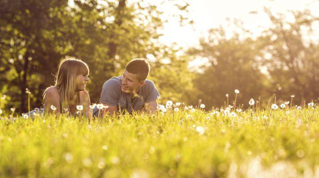 Eine junges Paar liegt auf einer Wiese.