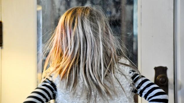 Rückansicht eines Kinds, dessen Haare statisch aufgeladen sind.