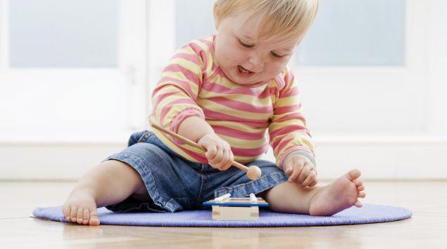 Ein Kleinkind spielt auf einem Xylophon.