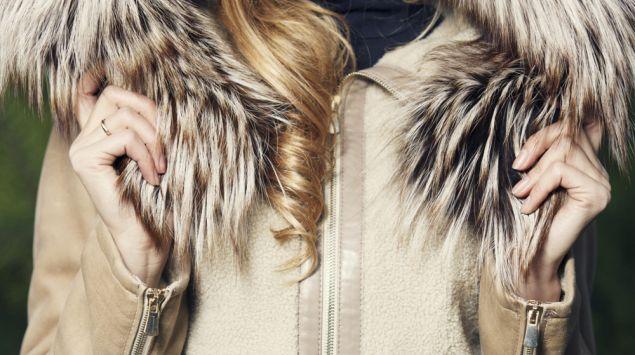 Das Bild zeigt eine Frau in einem warmen Wintermantel mit einer fellbesetzten Kapuze.