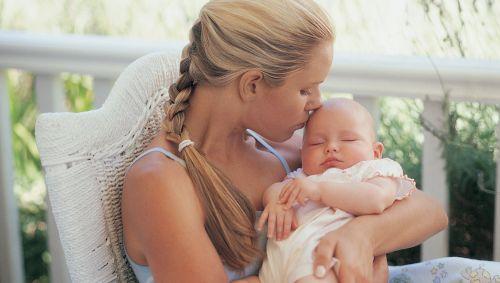 Mutter hält ihr Neugeborenes auf dem Arm und küsst die Stirn.