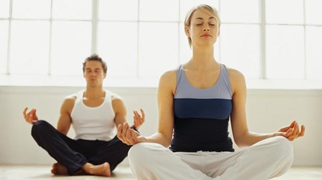 Das Bild zeigt eine Frau und einen Mann die Yoga machen.