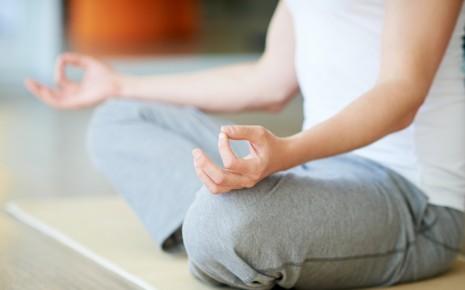Burnout: Man sieht einen Mann im Lotussitz bei der Mediation.