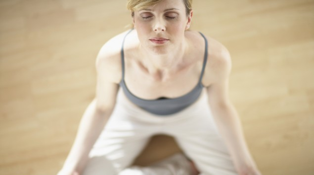 Man sieht eine Frau beim Yoga im Lotussitz.