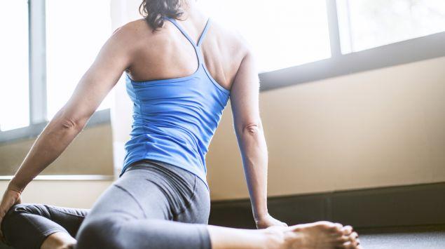 Man sieht eine Frau in einer sitzenden Yoga-Position.