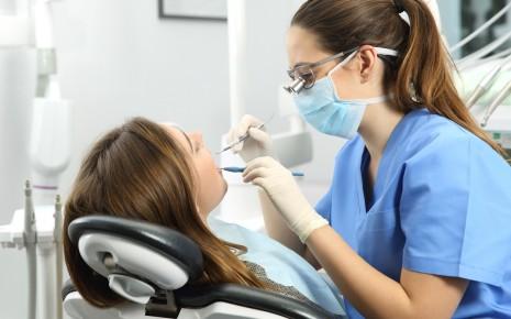 Professionelle Zahnreinigung: Eine Zahnärztin untersucht die Zähne einer Frau und trägt dabei eine Lupenbrille.