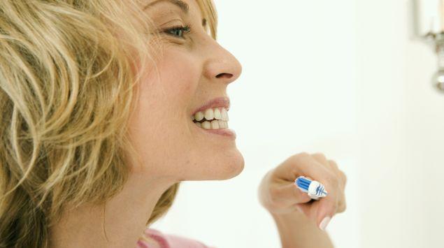 Man sieht eine Frau mit einer Zahnbürste, die ihre Zähne begutachtet.
