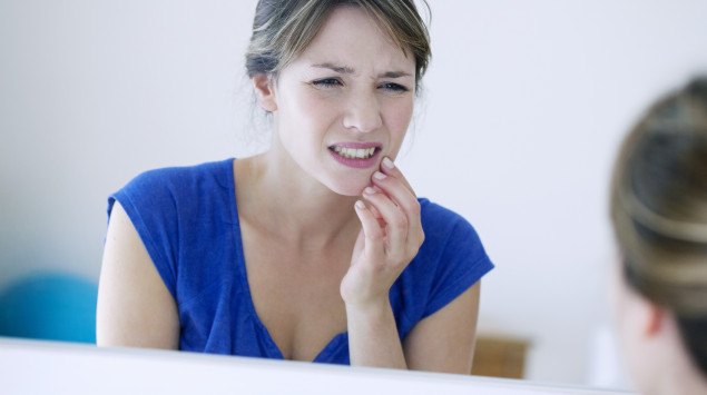 Eine Frau knirscht mit den Zähnen.
