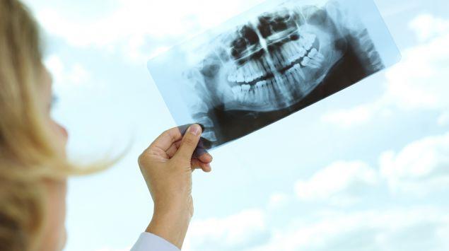 Eine Zahnärztin betrachtet ein Röntgenbild.