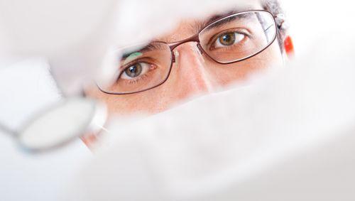 Ein Zahnarzt schaut in den Mund eines Patienten.