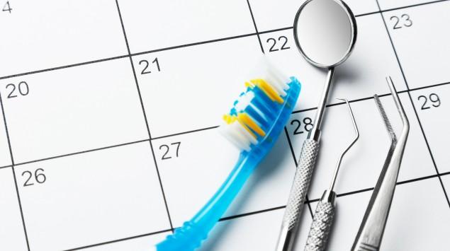 Zahnarzttermin: Man sieht eine Zahnbürste, einen Dentalsspiegel und andere Zahnarzt-Geräte auf einem Kalenderblatt.