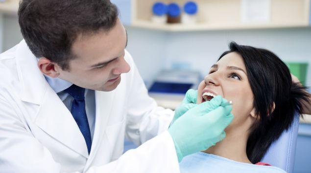 Man sieht eine Frau beim Zahnarzt.
