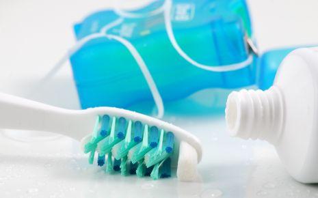 Parodontitis: Man sieht eine Zahnbürste, Zahnseide und eine Tube Zahnpasta.