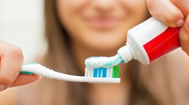 Man sieht eine Frau, die Zahnpasta auf eine Zahnbürste drückt.
