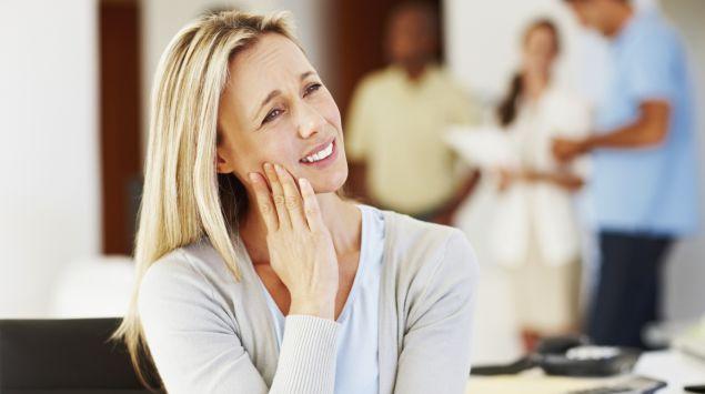 Man sieht eine Frau mit Zahnschmerzen.