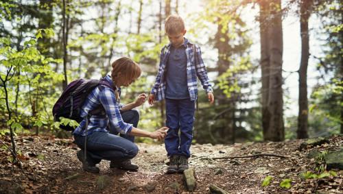 Eine Mutter sprüht Schuhe und Hosenbeine ihres Sohnes mit einem Zeckenschutzmittel ein.