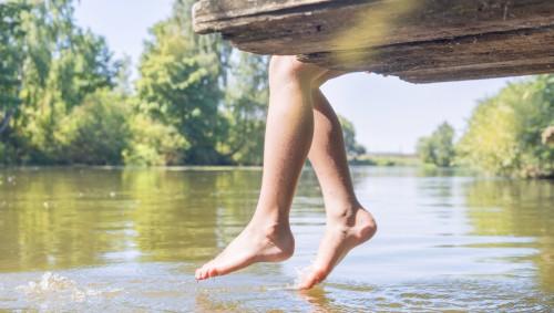 Jemand sitzt auf einem hölzernen Steg an einem See und hält seine Zehen ins Wasser.
