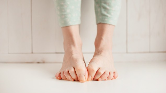 Frau versteckt ihre Zehen, auf dem Boden stehend