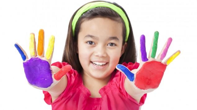 Ein Mädchen hält beide Hände, deren Innenflächen bunt bemalt sind, mit gespreizten Fingern in die Höhe.