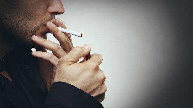 Ein Mann steckt sich eine Zigarette an.