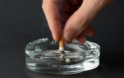 Jemand drückt eine Zigarette in einem gläsernen Aschenbecher aus.