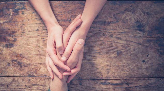 Jemand ergreift die Hände einer Person: Eine Depression wirkt sich auch auf die Angehörigen aus.