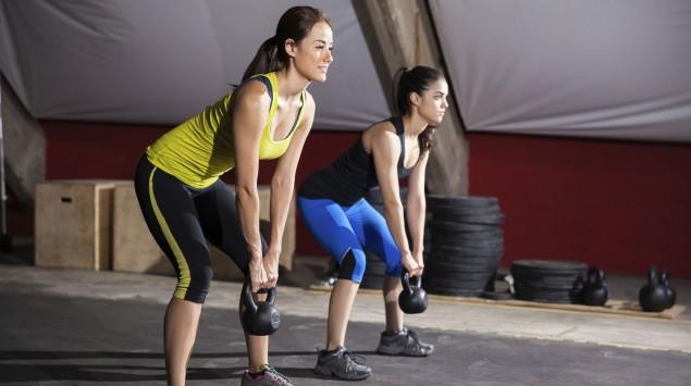 Das Bild zeigt zwei Frauen, die Übungen mit Kettlebells machen.