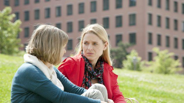 Zwei ältere Frauen sitzen auf einer Wiese und führen ein ernstes Gespräch.
