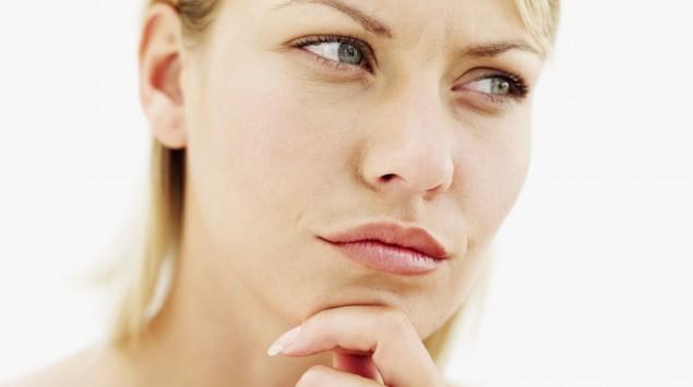 Eine Frau blickt anzweifelnd zur Seite.