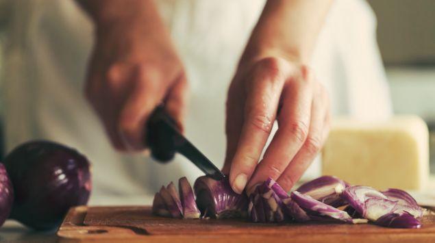 Eine Frau schneidet Zwiebeln.