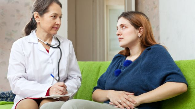 Frau mit Flankenschmerzen spricht mit Ärztin.